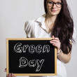 Green Day - Young businesswoman holding chalkboard...