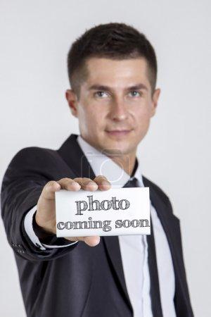 Photo pour Photo à venir bientôt - Jeune homme d'affaires tenant une carte blanche avec du texte - image verticale - image libre de droit