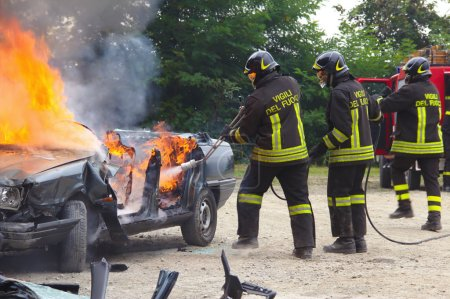 Firefighters extinguishing car on fire.