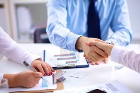 Photo pour Réunion d'affaires à la table serrant la main conclusion du contrat - image libre de droit