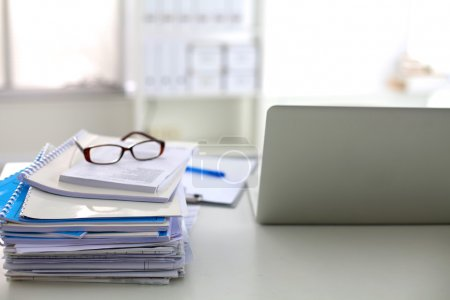Stack of papers and glasses lying on table desaturated