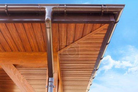 New brown copper gutter under a cloudy blue sky
