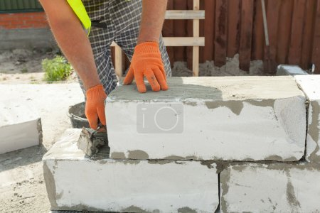 Bricklayer man worker in orange gloves installing aerated  block with trowel