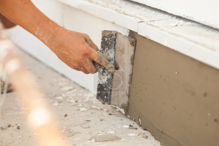 Man hand with trowel plastering a foundation of house