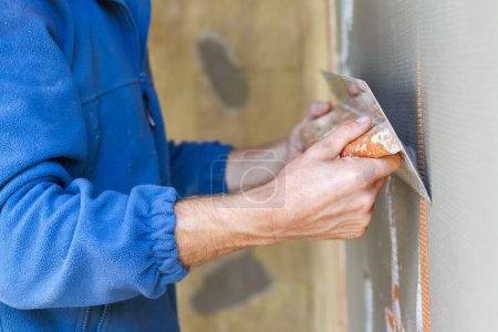 Construction worker with long trowel plastering a ...