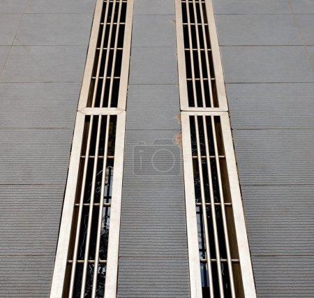 Photo pour Capturer la paire de fossés sales dont ils sont couverts par des grilles en acier inoxydable - image libre de droit