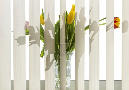Photo for Bouquet of flowers in a vase standing on the windowsill for vertical blinds - Royalty Free Image