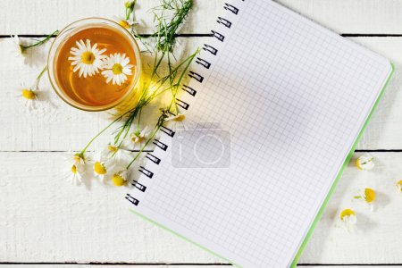 A glass of herbal tea with chamomile and a note pad, a top view