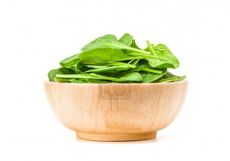 spinach leaf in wooden bowl isolated on white background
