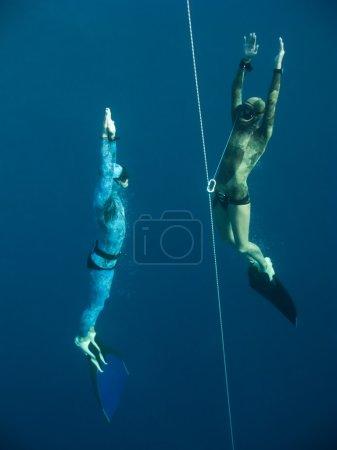 Photo pour Deux plongeurs s'élèvent de la profondeur près de la ligne de sécurité à Blue Hole, Dahab, Egypte - image libre de droit