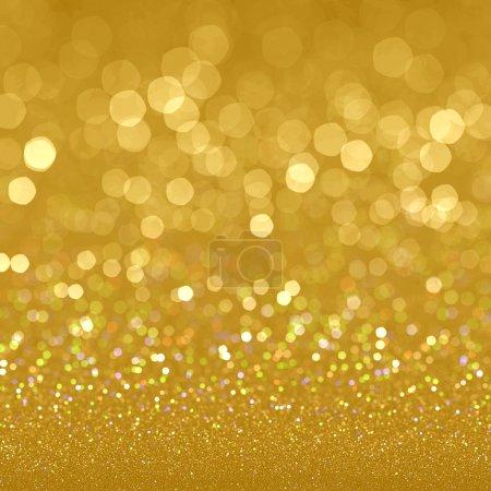 Golden festive glitter background with defocused lights