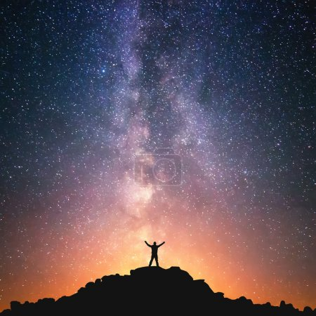 A person is standing on the top of the hill next to the Milky Way galaxy with his hands raised to the air.
