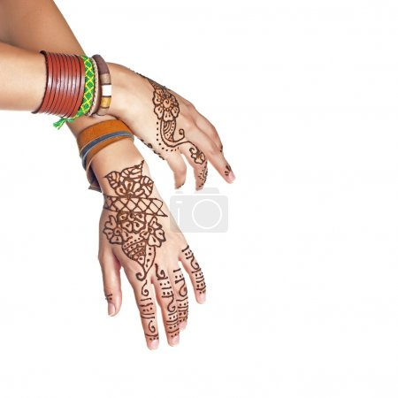 Mehendi or henna tatoo on the female hands in bracelets isolated