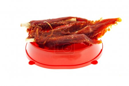 Few treats for dogs (meat, rawhide, bone) in red bowl isolated on a white background