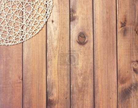 Round rope napkin or stand on a wooden rustic table. To create a