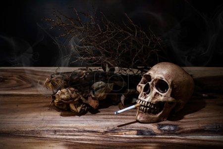 Nature morte crâne humain de fumer avec la cigarette sur la table en bois, p