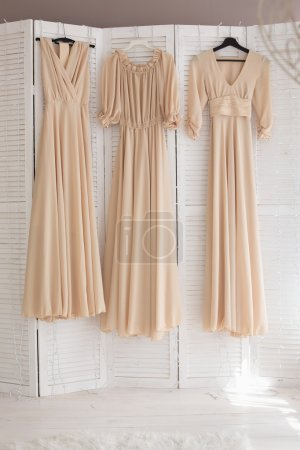 Photo pour Trois robes beiges pour demoiselles d'honneur accrochées à des cintres dans la chambre - image libre de droit
