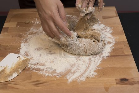 Foto de Mezcla de Susamielli Sweet del traditionale Italina Christnas. Fondo de madera cubierto con harina blanca. Amasa a mano - Imagen libre de derechos