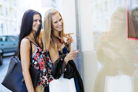 Photo pour Belles femmes faisant du shopping à l'extérieur et tenant des sacs - image libre de droit