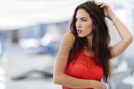 Glamorous woman posing in red dress