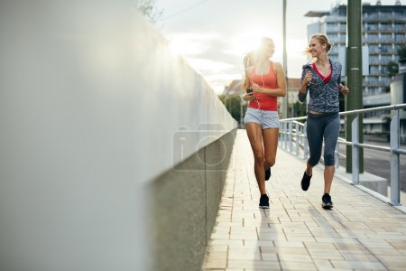 Photo for Two women exercising by jogging in the city while sun is setting - Royalty Free Image