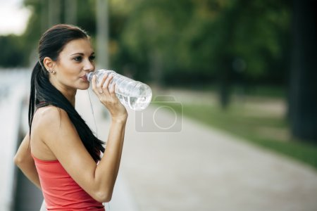 Photo for Thirsty woman drinking water to recuperate after jogging - Royalty Free Image
