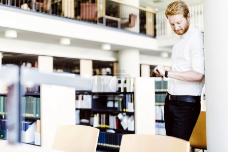 Student checking time in library