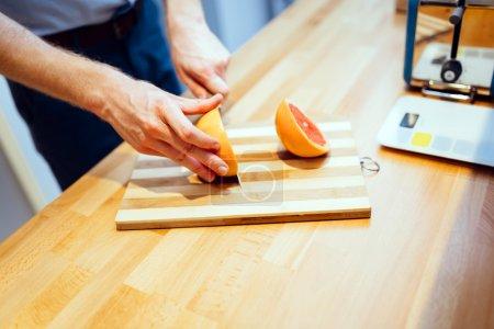 Man slicing orange in kitchen