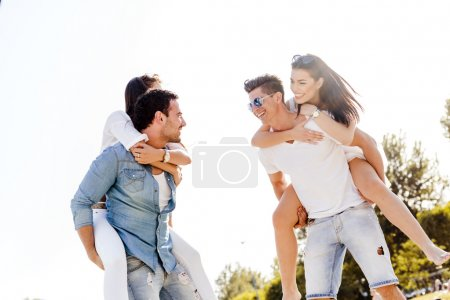 Photo for Group of young happy people carrying women on a sandy beach piggyback - Royalty Free Image