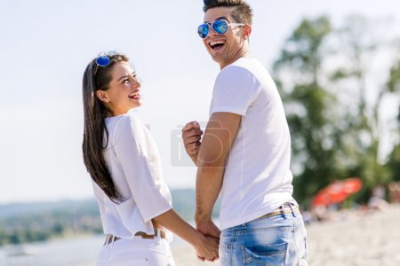 Photo for Young couple holding hands and walking on a beach - Royalty Free Image