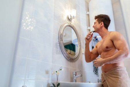 Handsome man shaving in bathroom