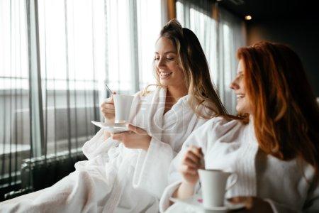Women in bathrobes enjoying tea