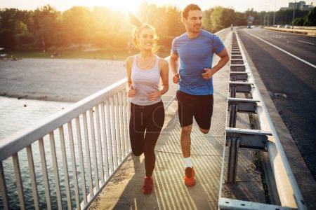 Photo for Beautiful couple in motion running over bridge - Royalty Free Image