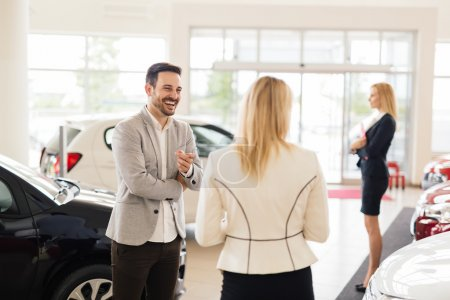 Photo for Customer looking at cars at dealership and talking to salesperson - Royalty Free Image