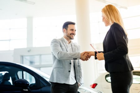 Photo for Salesperson showing vehicle to potential customer and shaking hands in dealership - Royalty Free Image
