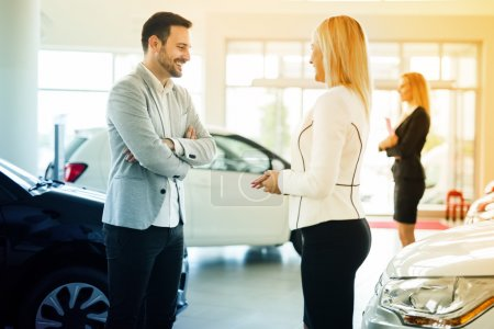 Photo for Salesperson showing vehicle to potential customer in dealership - Royalty Free Image