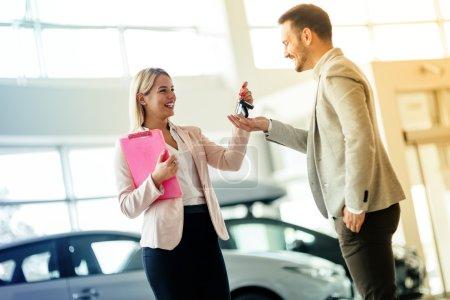 Photo pour Un client heureux vient d'acheter une voiture chez un concessionnaire automobile . - image libre de droit