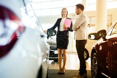 Photo for Car salesperson assisting customer at car dealership - Royalty Free Image