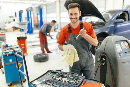 Photo pour Mécanicien automobile réparer une voiture dans le garage chez le concessionnaire - image libre de droit