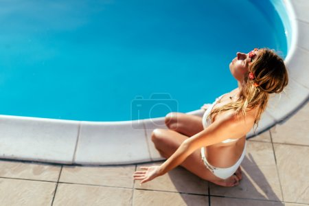 Blonde woman meditating at pool
