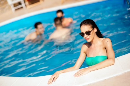 Beautiful woman and friends in pool