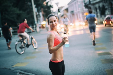 Thirsty sportswoman drinking water