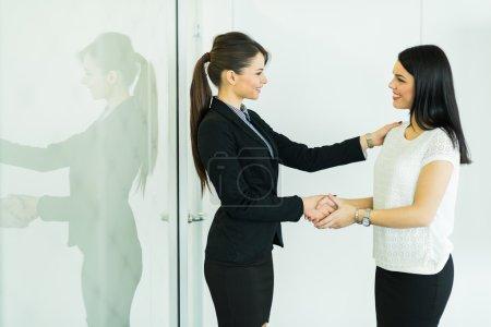 Two businesswomen shakig hands in an office