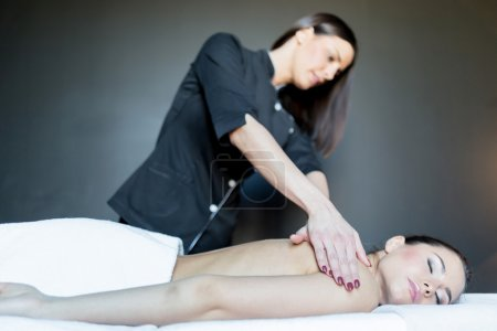 Massage therapist massaging a stunning lady