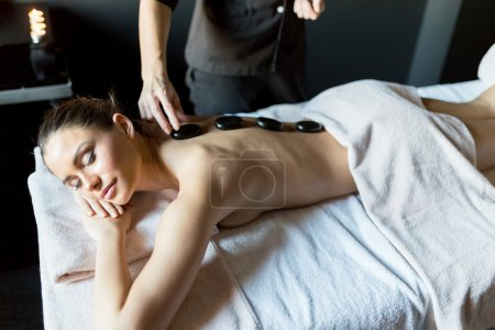 Masseur placing hot stones onto lady's back