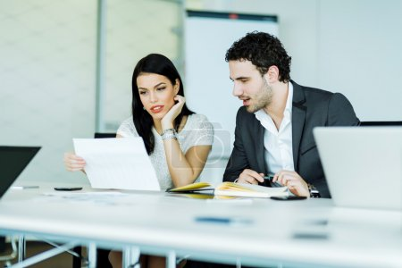 Businesswoman and  businessman looking at a paper