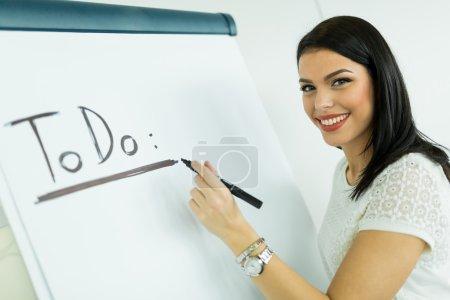 Businesswoman writing todo onto a writing board