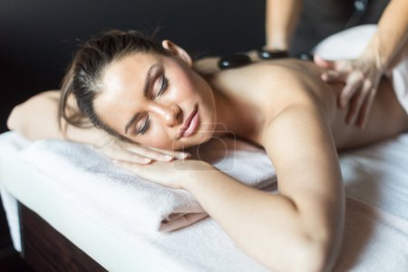 Woman being massaged with hot stones