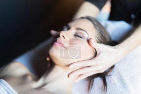 Masseur massaging face of woman