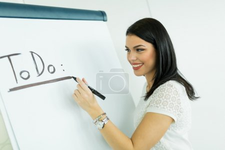 Businesswoman writing todo onto a writing board